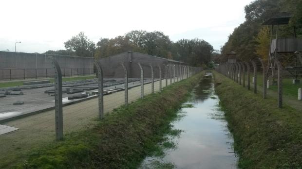 Je ziet op de foto de gracht die door gevangenen is gegraven. Rechts zie je de wachttoren, waar vooral Nederlanders in zaten die de kant van de Duitsers gekozen hadden.